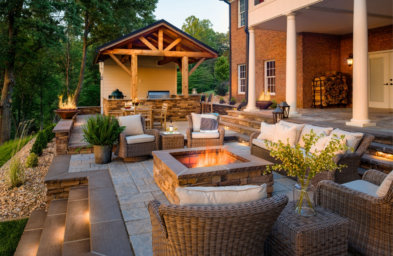 patio with fire pit and outdoor kitchen by Land Tech Group